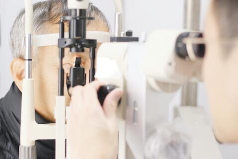 Older man having eyes checked for diabetic retinopathy.