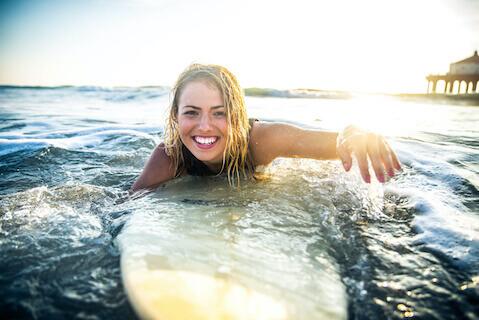 Woman paddling on surfboard